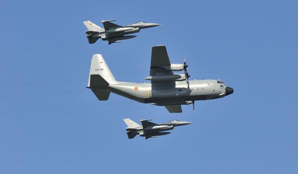 Belgische C-130 Hercules onder begeleiding van F-16's.