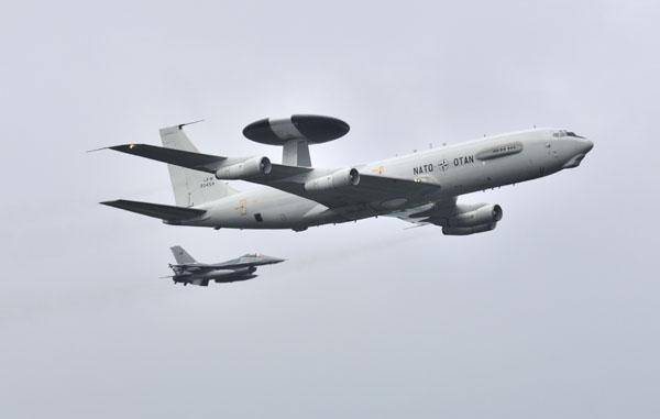 NATO E-3 AWAC's met een F-16AM langzij in de ochtendnevel.